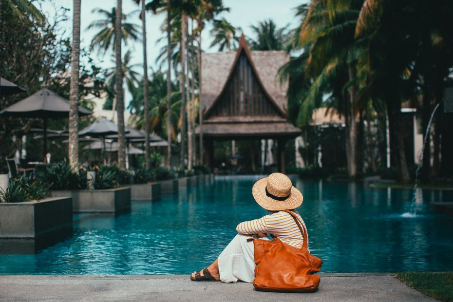 unrecognizable woman sitting on poolside in peaceful resort