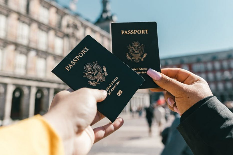 anonymous tourists showing us passports on street on sunny day